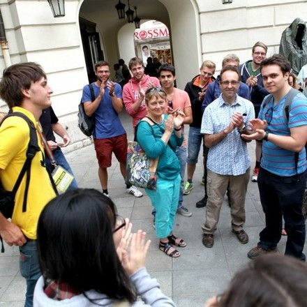 Group of travelers applauding a free walking tour guide in Prague.