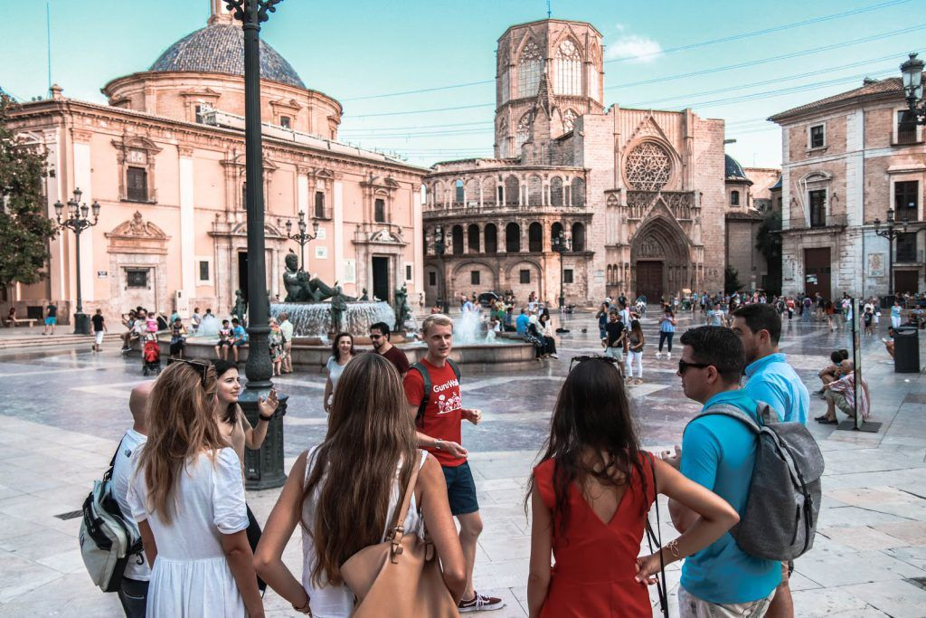 Foto con filtro de un guía explicando en una plaza en Valencia