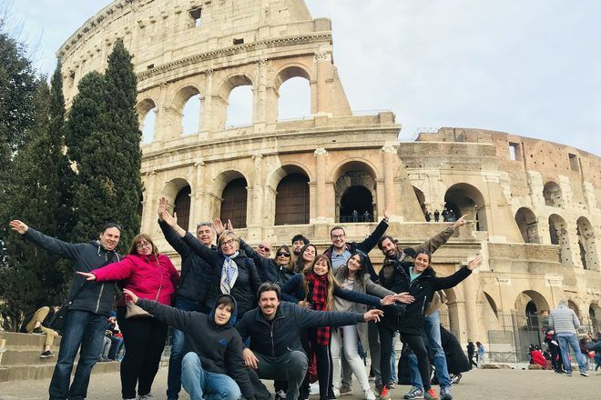 Travelers taking a group picture in front of the Colosseum during a free walking tour in Rome.