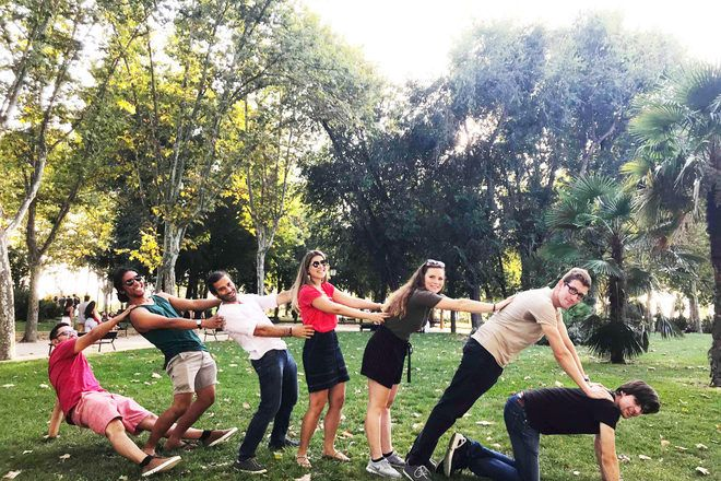 Travelers doing a funny picture during a free walking tour in a park in Madrid, Spain.