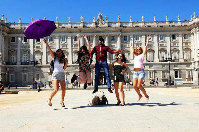 Group of travelers jumping in the air during a free walking tour in Madrid, Spain.
