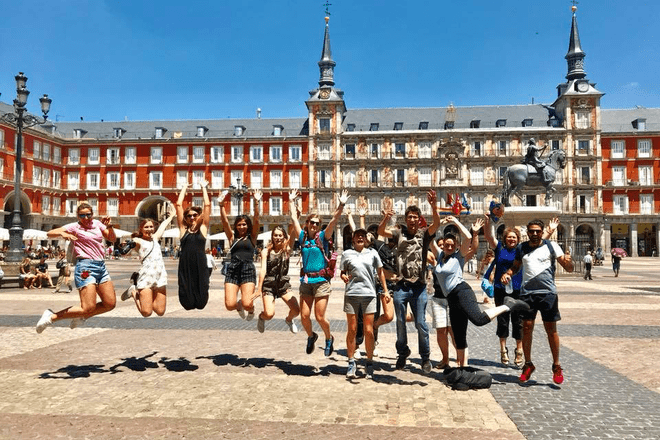 Travelers jumping in the air during a free walking tour in Madrid, Spain.