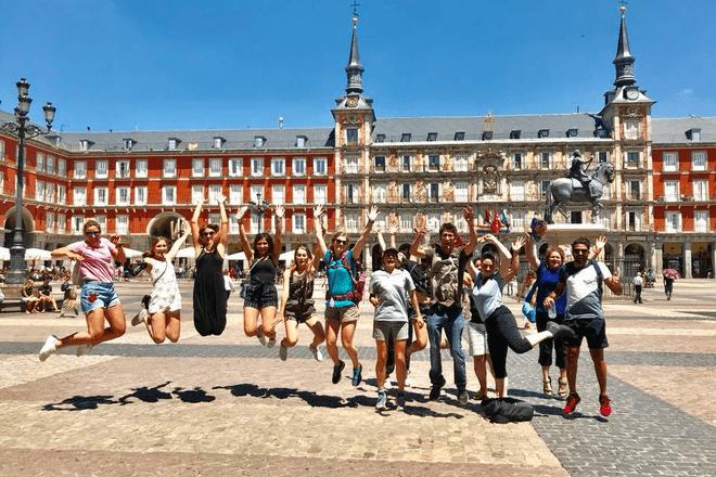 Grupo de viajeros saltando en la Plaza Mayor de Madrid durante un free tour.