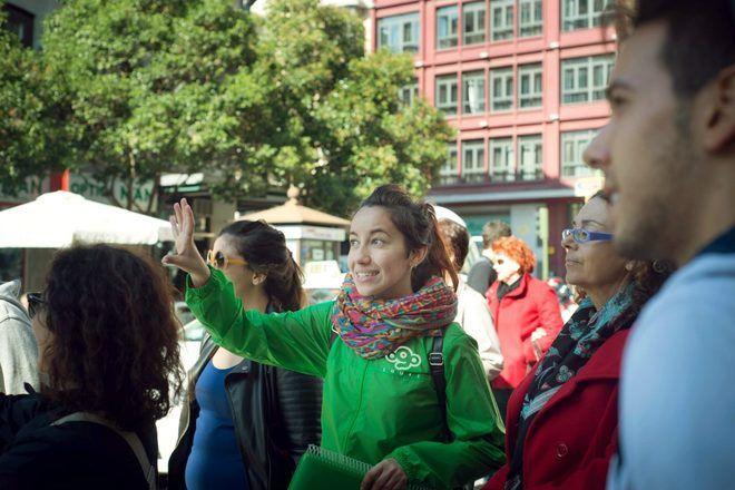 Guía enseñando algo a los viajeros durante un guruwalk en Madrid, España