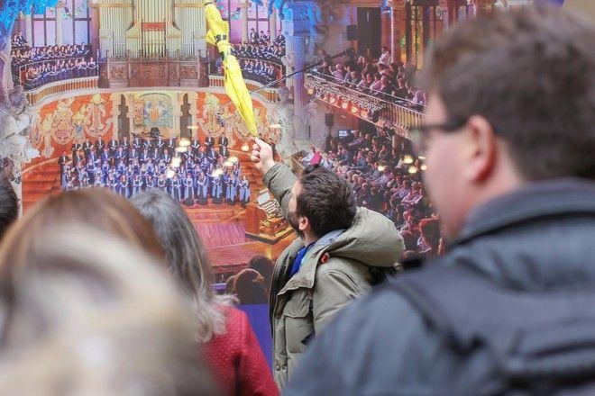 Guía enseñando algo con su paraguas a un grupo de viajeros durante un free tour en Barcelona.
