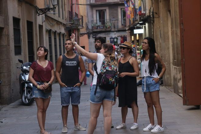 Guía explicando algo a los viajeros en el casco antiguo de Barcelona en España durante un free tour.