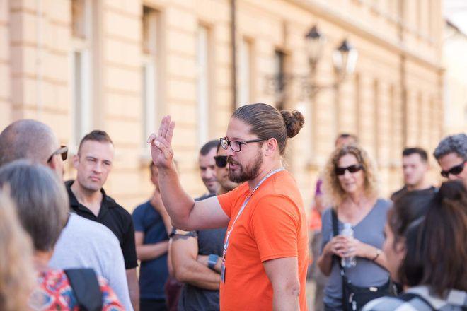 Guía explicando algo a los viajeros haciendo 3 con sus dedos durante un free tour con GuruWalk.