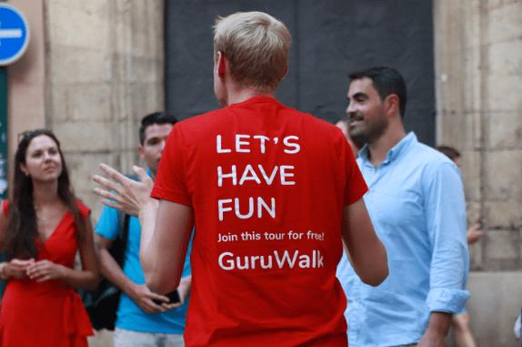Guía de free tour de espalda con una camiseta de GuruWalk invitando la gente a unirse al tour.
