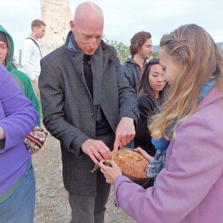 Guía de free tour de GuruWalk ofreciendo un pan a sus viajeros durante un tour en Atenas.