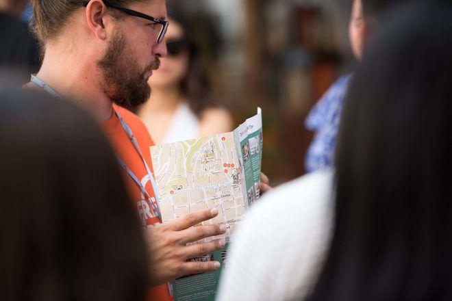 Guía de free tour usando un mapa para enseñar algo a los viajeros.