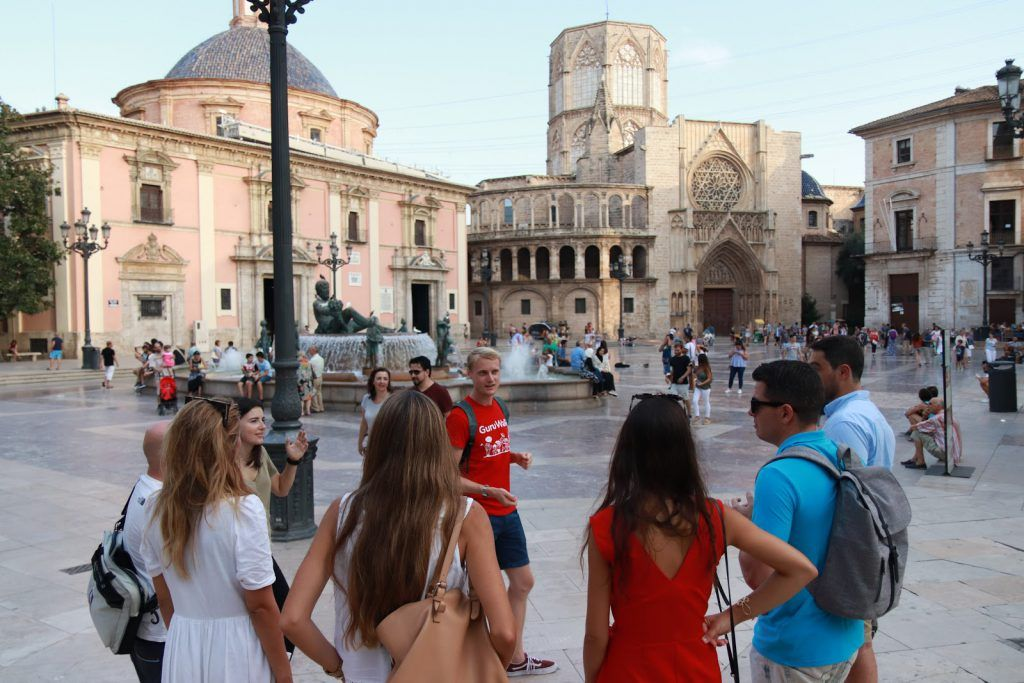 A guide explaining on a square in Valencia during a guruwalk