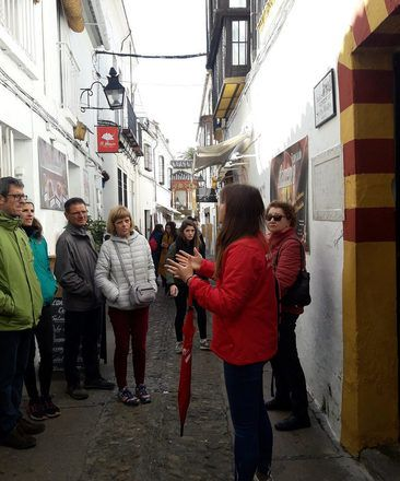 A guide explaining something in a street of Cordoba, Spain, during a free walking tour with GuruWalk.
