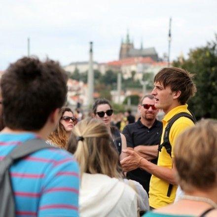 Free walking tour guide in Prague explaining something to a group of travelers.