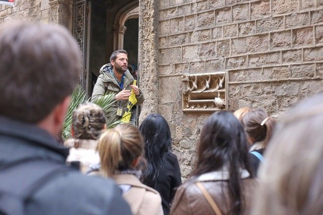 Guide speaking to a group of travelers during a free walking tour in Barcelona, Spain.