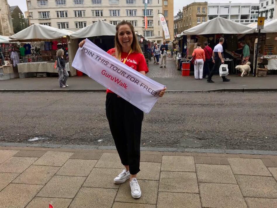 Guía de free tour en Cambridge invitando los viajeros a unirse al tour con una bandera de GuruWalk.