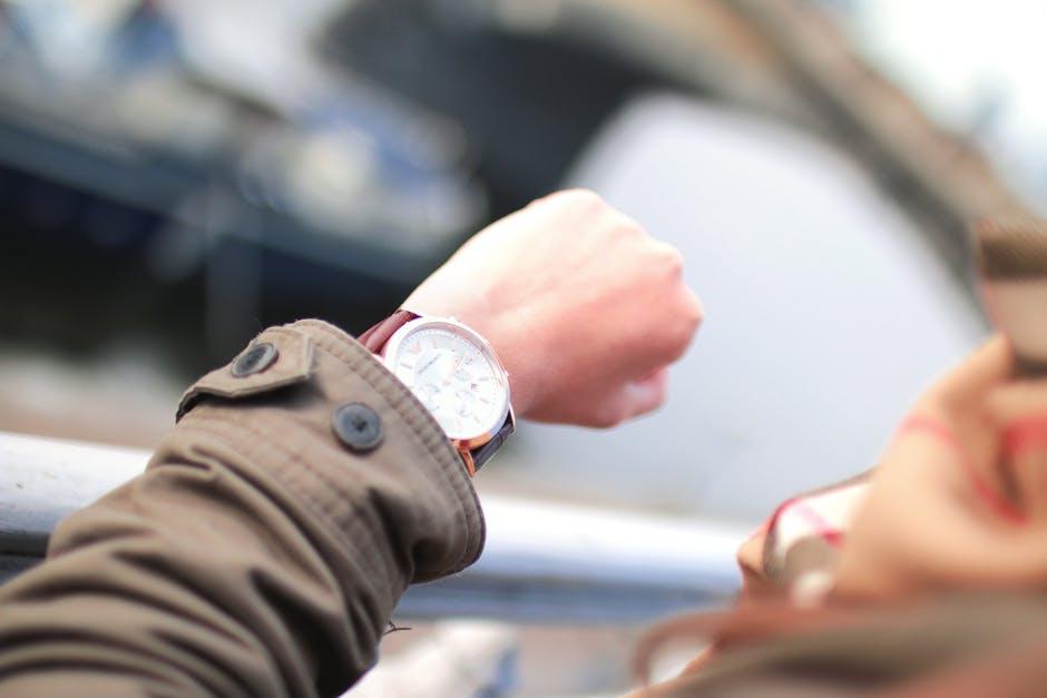 Una persona mirando su reloj, esperando.
