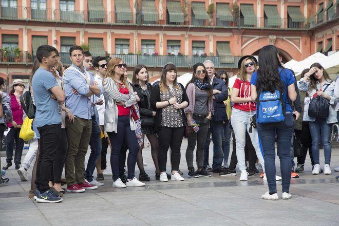 Guía de free tour en Córdoba explicando algo a su grupo en la Plaza de la Corredera.