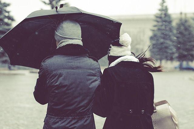2 viajeros que se protegen de la nieve y del viento con un paraguas negro.