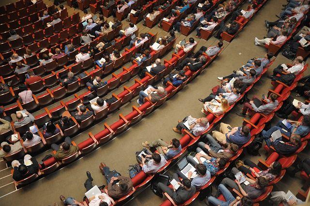 Gente sentada asistiendo en una conferencia.