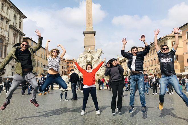 Travelers jumping in the air in a famous place of Rome during a free walking tour with GuruWalk.