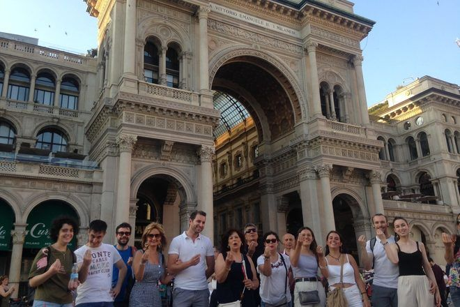 Travelers taking a group picture doing a very typical italian gesture on a free walking tour in Milan, Italy.
