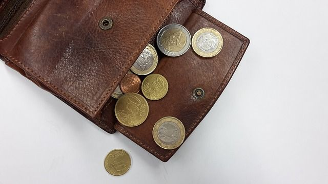 Wallet full of coins in euros.