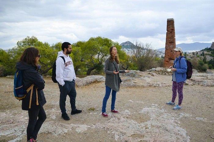 Guía de free tour de Atenas explica algo a sus viajeros en un lugar verde.