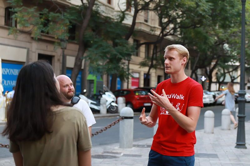 Guide of GuruWalk explaining something to travelers on a free walking tour in Valencia, Spain.