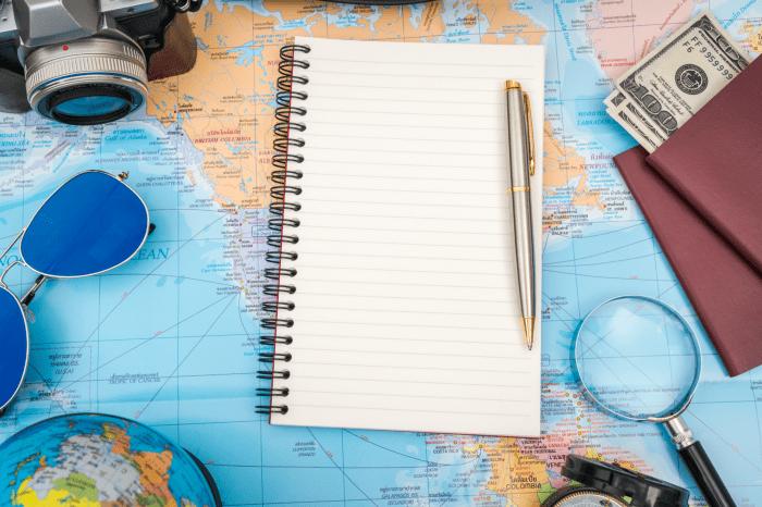 Libro blanco con un boli en un mapa del mundo para preparar un viaje.