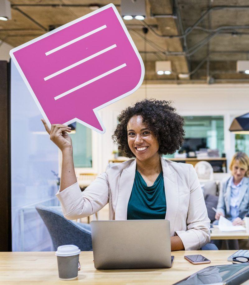 Mujer con un cartel rosa haciendo como si está hablando.