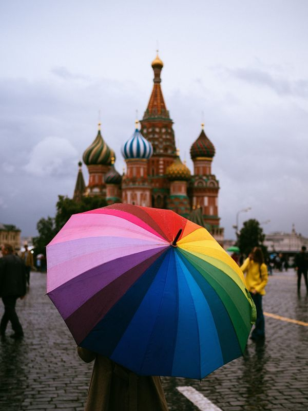 Someone holding a rainbow umbrella in the red square of Moscow, waiting for a free walking tour or guruwalk.