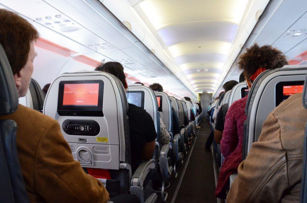 Vista dentro de un avión en vuelo, del pasillo, los pasajeros sentados.