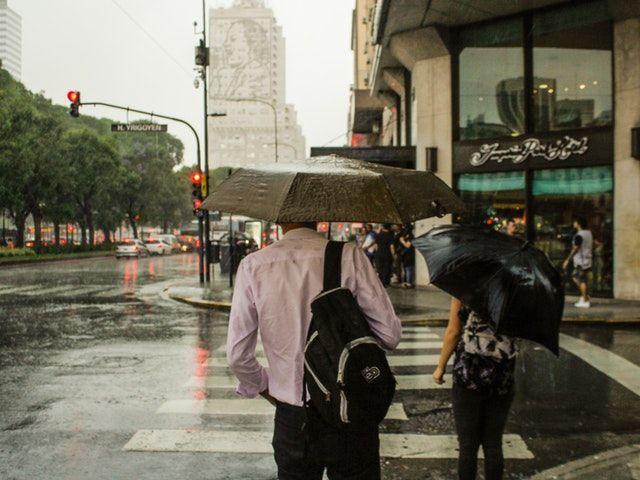 Hombre caminando por una calle bajo la lluvia con un paraguas.