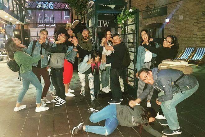 Grupo de viajeros que toma una foto chistosa matando entre ellos durante un free tour de Jack El Destripador con GuruWalk.