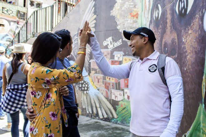 A guide gives a highfive to travelers during a free walking tour with GuruWalk.