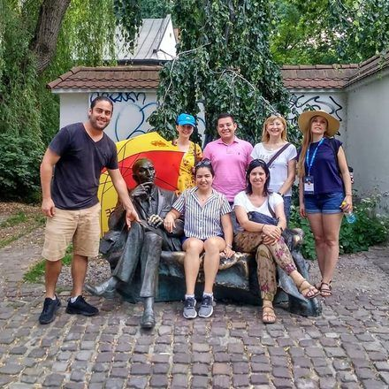 Group of travelers taking a photo with a Krakow monument during a free tour with GuruWalk.