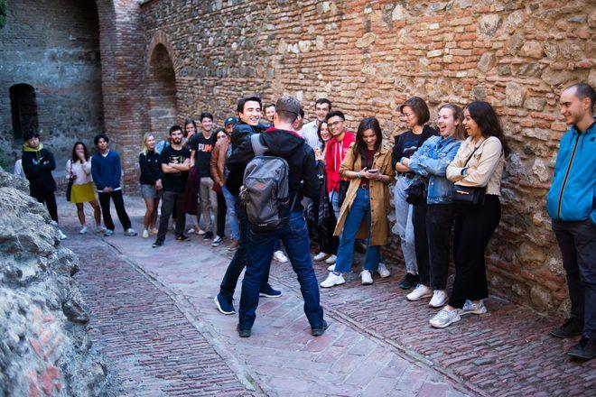 Un guía de free tour de Málaga hace participar los viajeros durante una parada.
