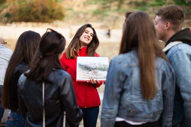 Un guía de free tour explica algo a los viajeros enseñando una foto durante un guruwalk en Málaga.