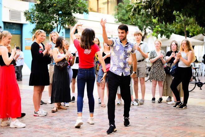 Un guía de free tour enseña como bailar sevillana a un grupo de viajeros en Málaga.