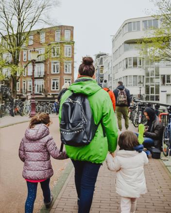 Un guía de free tour dando la mano a niños en Amsterdam.