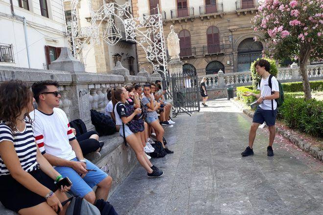 Guía de free tour explica algo a los viajeros sentados.