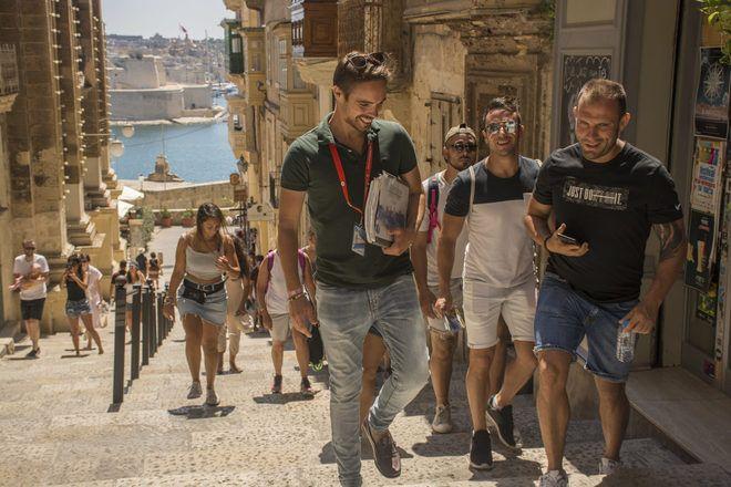 Guía hablando con un viajero mientras camina de un punto a otro durante un free tour en Malta con GuruWalk.