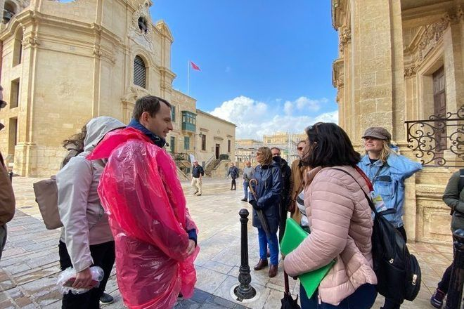Tour guide speaking to a traveler wearing a plastic coat during a free walking tour in Malta with GuruWalk.