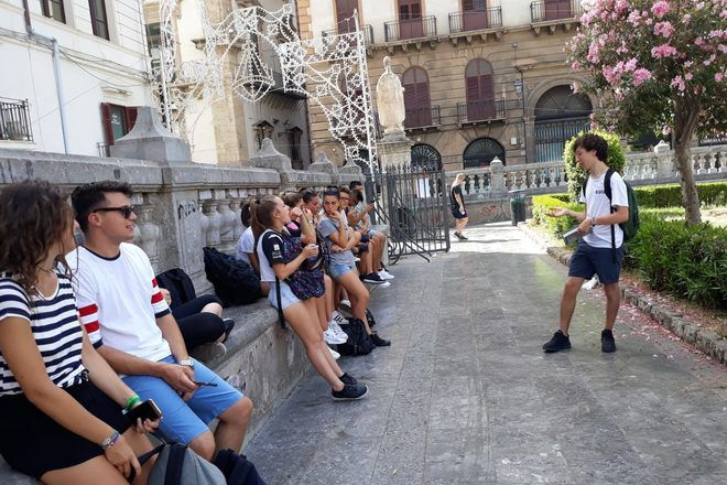 A guide explaining something to travelers sitted.
