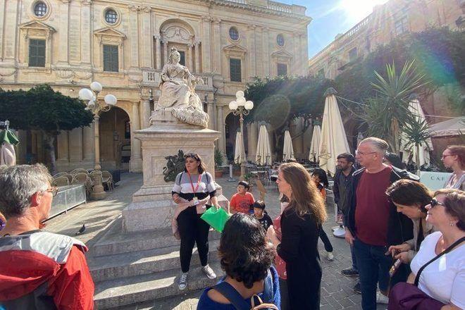 Guía de free tour en Malta explicando la historia de una estatua a los viajeros.
