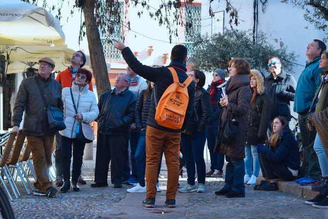 Guía de free tour con una mochila naranja explica algo a los viajeros