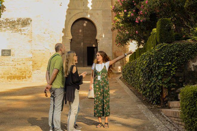 Guía de free tour de GuruWalk explicando algo a un pareja de viajeros en Andalucía.