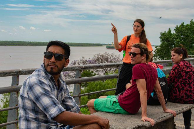 Guía de free tour de GuruWalk explicando algo a los viajeros sentados con una bonita vista.