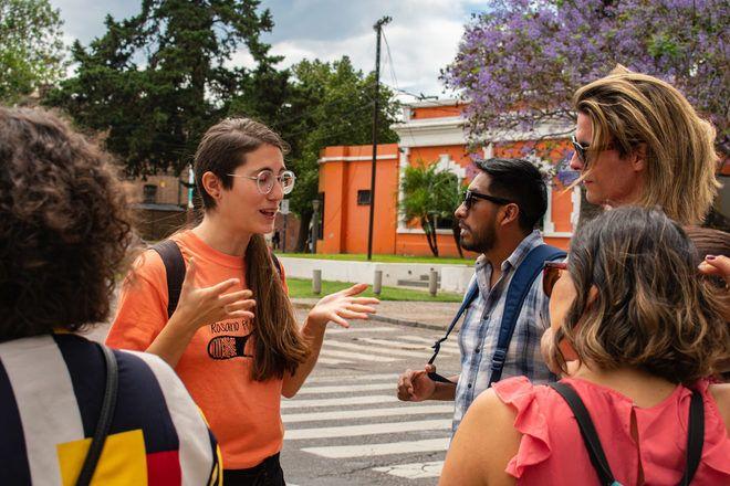 Guía de free tour de Rosario en Argentina explica algo a su grupo de viajeros.
