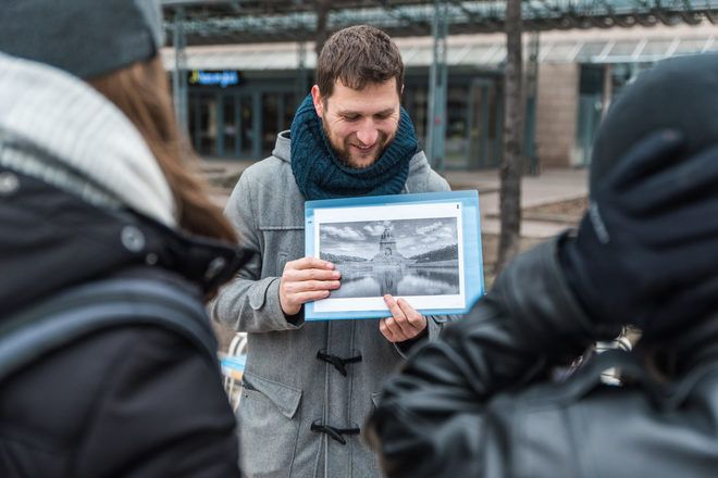 Guide showing a picture to travelers during a free walking tour with GuruWalk in Leipzig, Germany.